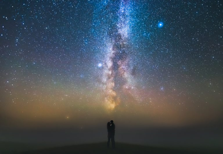 Landscape with Milky way galaxy and couple standing against the stars